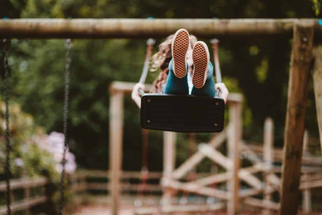 Young girl swinging on a wooden swingset at the park
