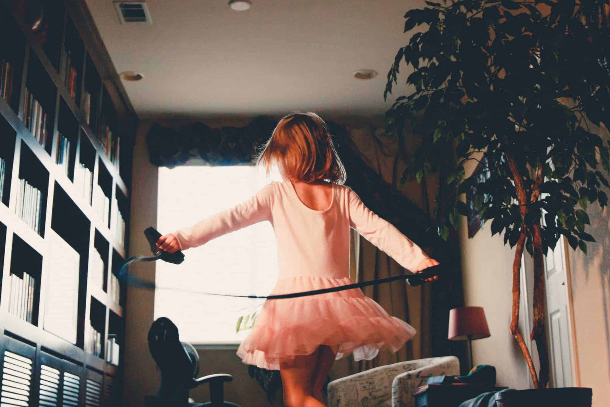 A little girl in a pink tutu dress, swing a jump rope behind her back in the family reading room.