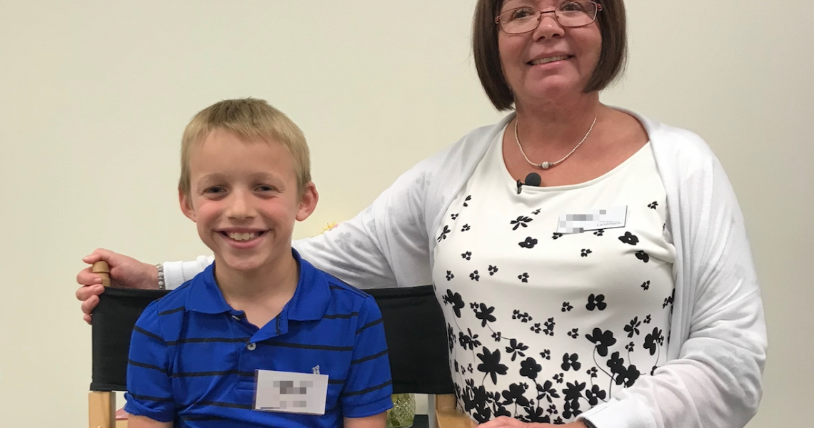 9-year-old boy smiling with his instructor after completing the Landmark Forum for Young People