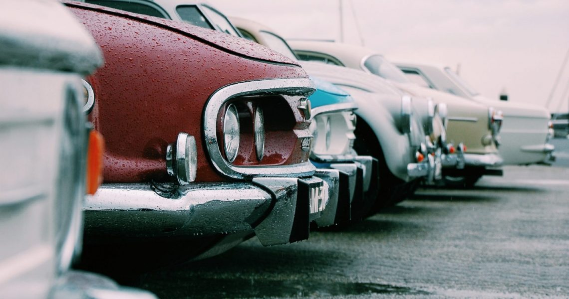 The front end of 7 classic cars lined up in a row